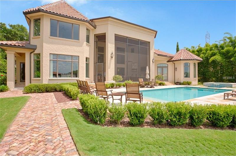 This is a look at the back of the house with beige exterior walls adorned by the large glass windows and walls. This is foregrounded by the pool and the surrounding landscape of grass lawns, shrubs and brick walkways. Image courtesy of Toptenrealestatedeals.com.