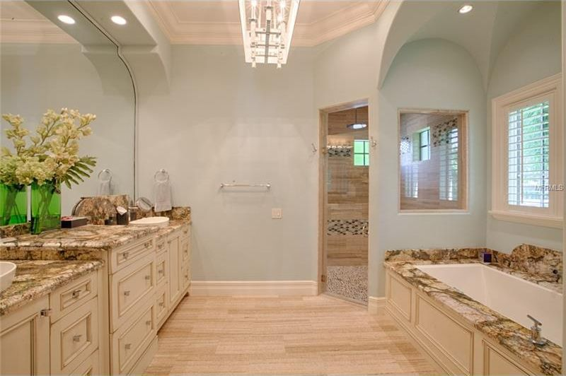 This is the bathroom with a large beige beige bathtub in its own alcove with windows across from the two-sink beige vanity. Image courtesy of Toptenrealestatedeals.com.
