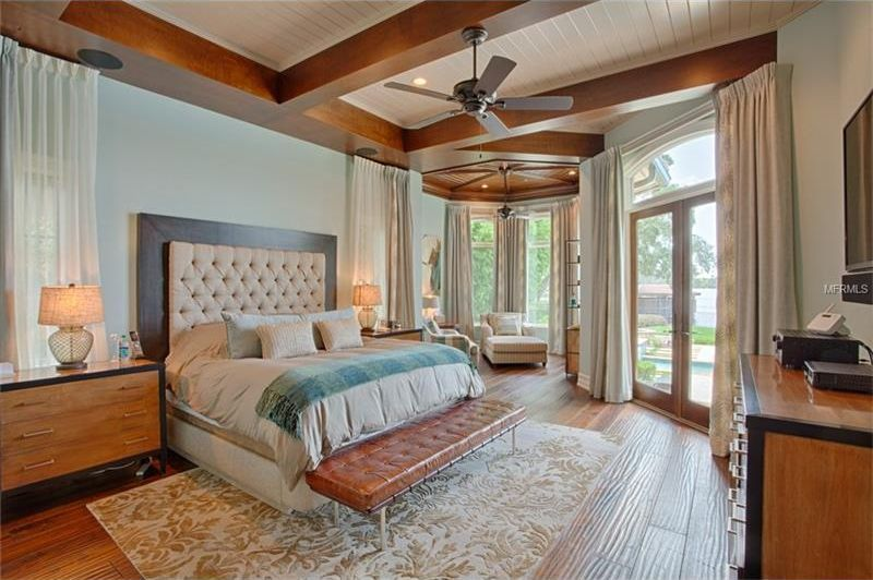 This bedroom has a large bed that has a beige tufted headboard. This is topped with a beige ceiling adorned by large wooden beams. Image courtesy of Toptenrealestatedeals.com.