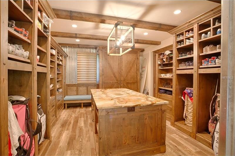 The spacious walk-in closet has a large wooden island in the middle surrounded by built-in wooden shelves and cabinets. Image courtesy of Toptenrealestatedeals.com.