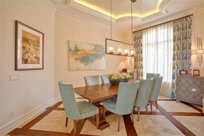 This is the formal dining room with a large wooden dining table complemented by the surrounding gray cushioned chairs. Image courtesy of Toptenrealestatedeals.com.