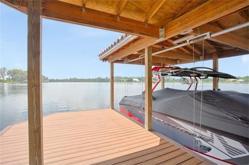 The property also has a wooden private lake dock with a wooden ceiling and wooden walkway over the water. Image courtesy of Toptenrealestatedeals.com.