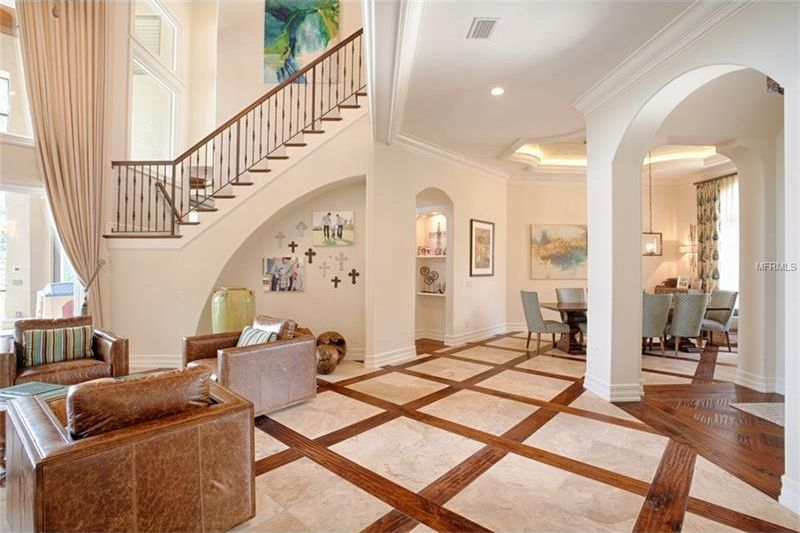 Upon entry, you are welcomed by this large foyer with beige marble flooring to match the beige arches and pillars. Image courtesy of Toptenrealestatedeals.com.