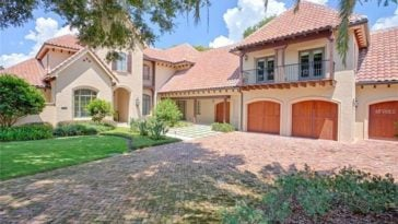 This is the front of the house with beige walls adorned by the terracotta roof tiles, large garage doors and the landscape that has a wide brick driveway and shrubs. Image courtesy of Toptenrealestatedeals.com.