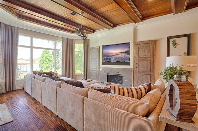This is a closer look at the living room area of the great room with a large beige sectional sofa across from the built-in wooden structure that houses the TV. Image courtesy of Toptenrealestatedeals.com.