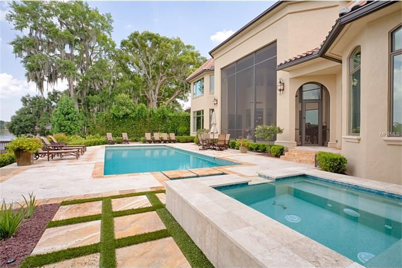 This is a look at the swimming pool and the smaller spa-type pool beside it. This also shows the back of the house with beige exteriors complemented by the large glass wall and the tall trees at the far side. Image courtesy of Toptenrealestatedeals.com.
