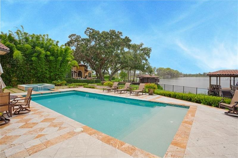 This is a closer look at the backyard pool surrounded by beige tiles and various sitting areas. You can also see here the lake view from the edge of the backyard. Image courtesy of Toptenrealestatedeals.com.