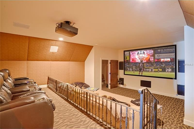 This is the home theater room with a large wall-mounted screen across from the rows of ascending beige sofas that match the beige walls and ceiling. Image courtesy of Toptenrealestatedeals.com.