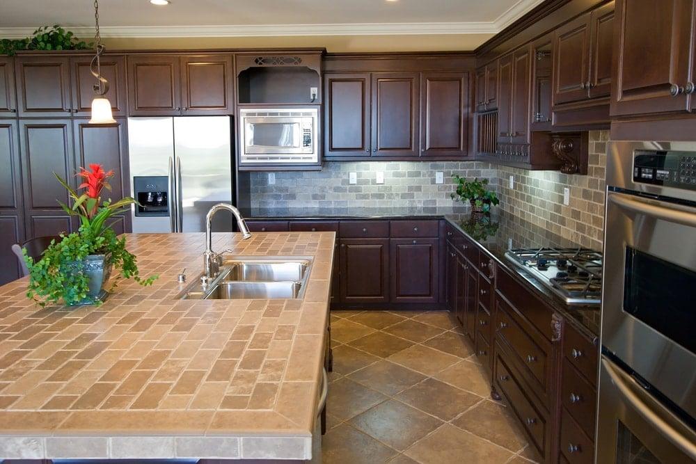 Luxury kitchen with tile island countertop and tile backsplash.