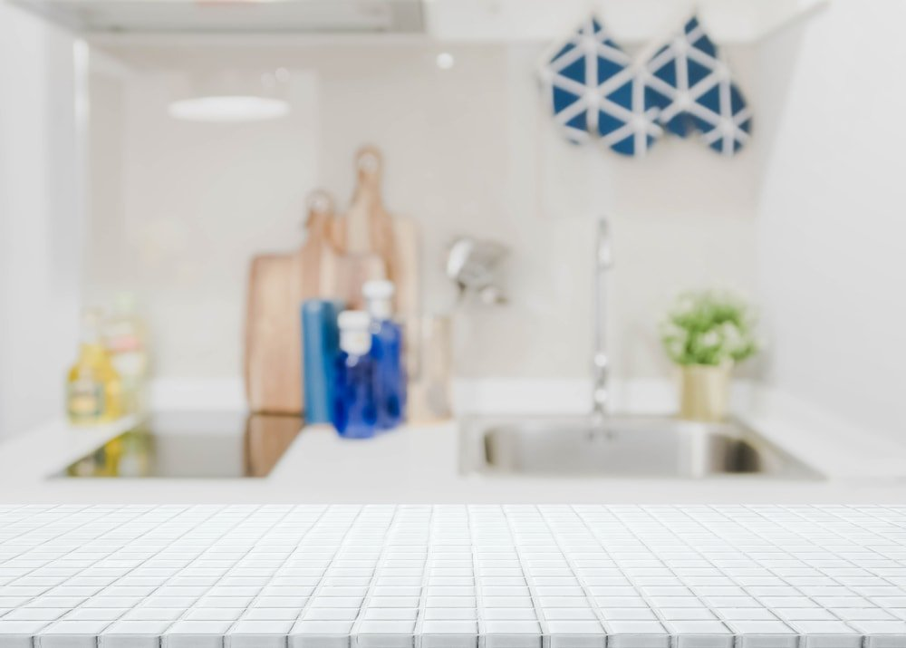 White ceramic tile countertop and blurred kitchen interior background