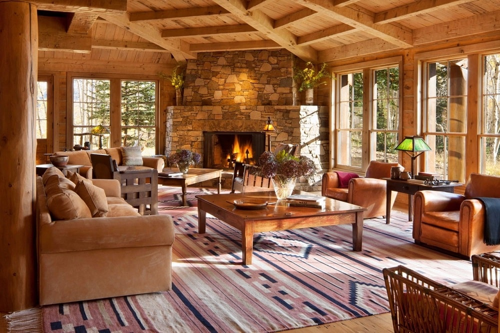 This is the spacious living room with a massive stone fireplace flanked by glass walls across from various sofas and wooden coffee tables. Image courtesy of Toptenrealestatedeals.com.