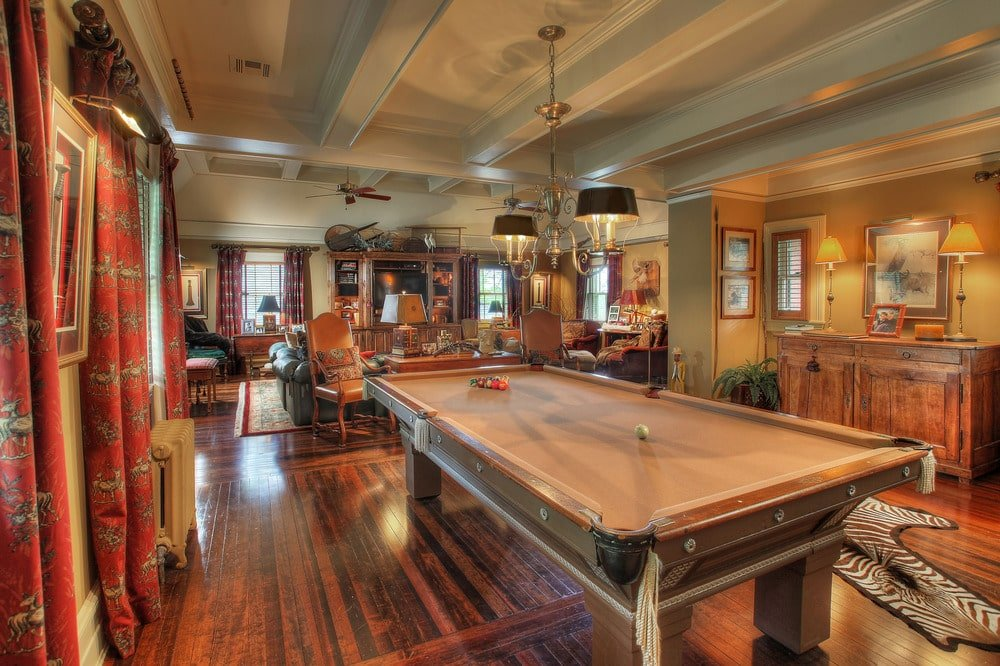 The game room has a vintage wooden pool table and a grand piano on dark hardwood flooring. Image courtesy of Toptenrealestatedeals.com.