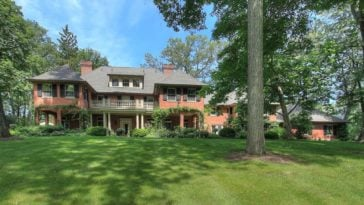 This is a front view of the Georgian-style mansion with dormer windows and a large balcony on the second level. These are then complemented by the surrounding landscape of tall trees and grass lawn. Image courtesy of Toptenrealestatedeals.com.