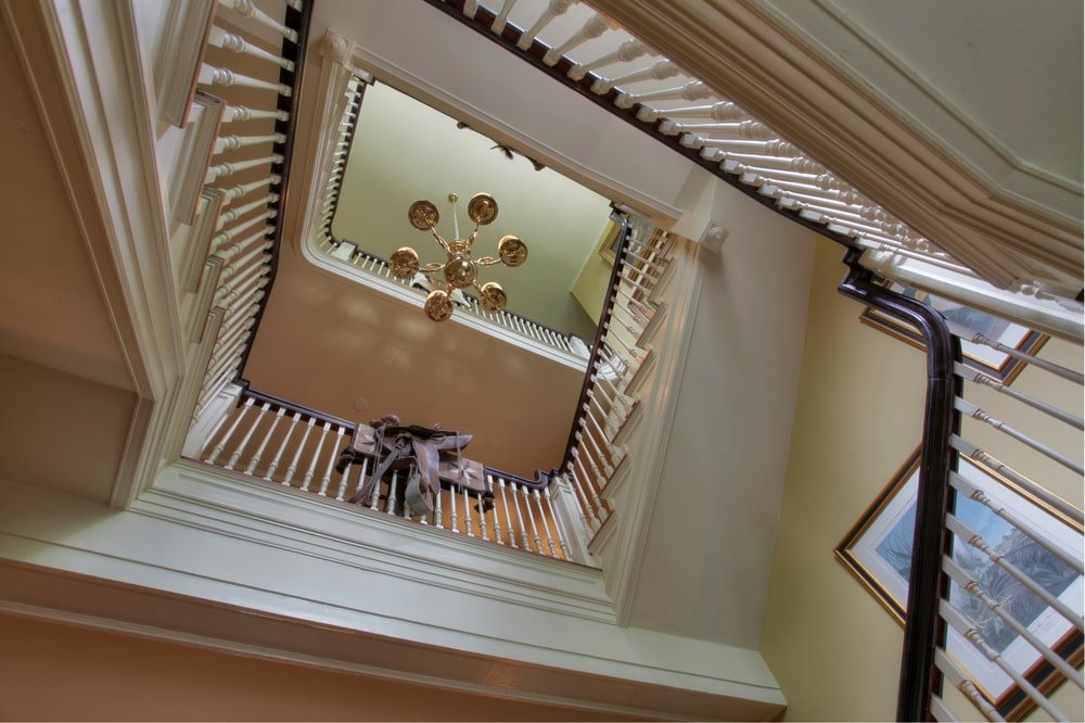 This is a look at the indoor balcony of the mansion from the vantage of the lowest floor. You can see here the tall ceiling with a chandelier and the wooden railings of the indoor balcony. Image courtesy of Toptenrealestatedeals.com.