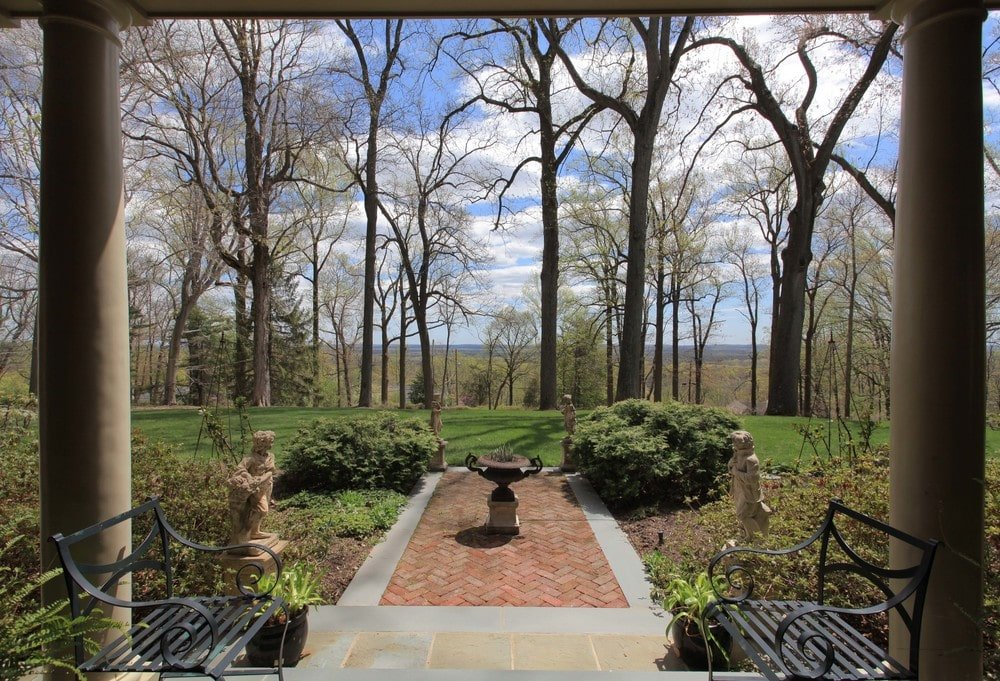 This is a look at the back of the house with a small covered patio that has a couple of iron benches and a view of the fountain adorned by shrubs and trees.. Image courtesy of Toptenrealestatedeals.com.