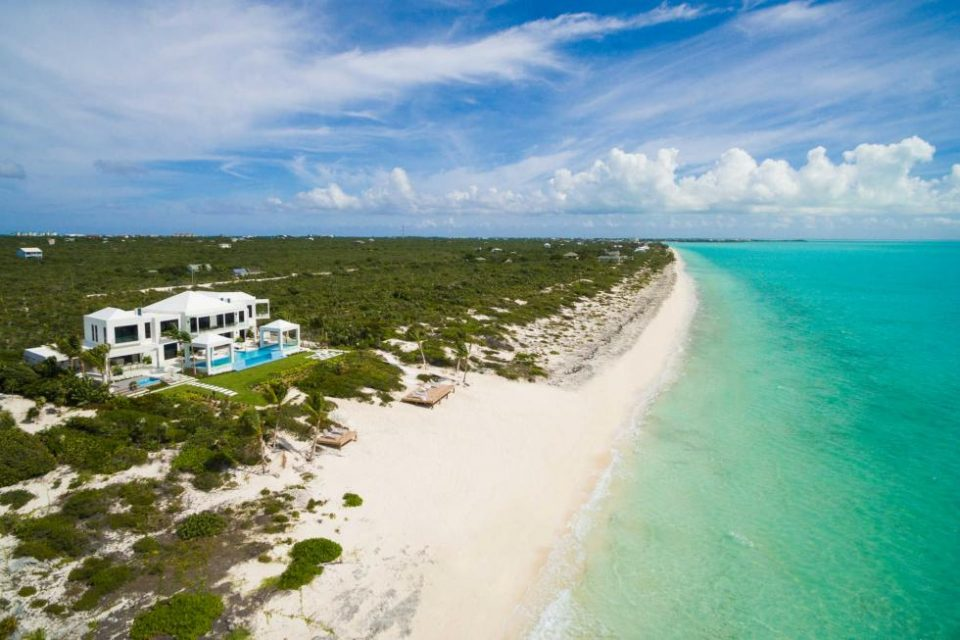This aerial view of the beach house features the long stretch of white sandy beach just a few yards from the back of the house. Image courtesy of Toptenrealestatedeals.com.