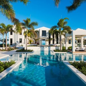 This is a look at the back of the house with white exterior walls, various poolside structures and a large pool adorned with tall tropical trees. Image courtesy of Toptenrealestatedeals.com.