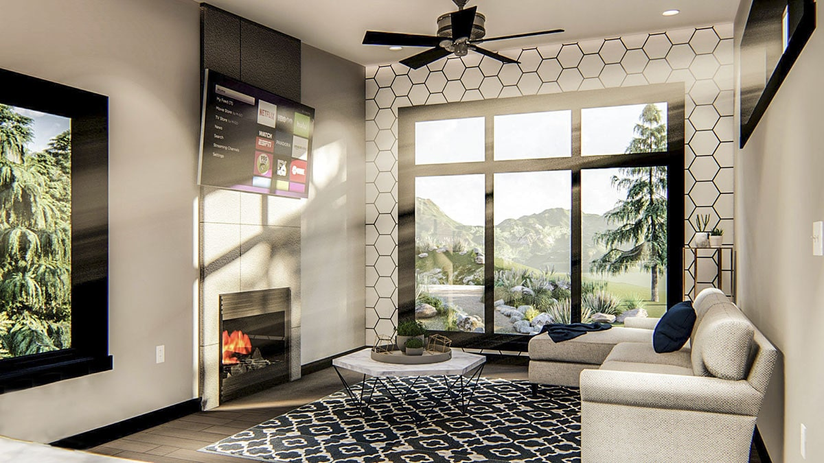 Living room with an L-shaped sofa, hexagonal coffee table, modern fireplace, TV, and massive windows overlooking the outdoor scenery.