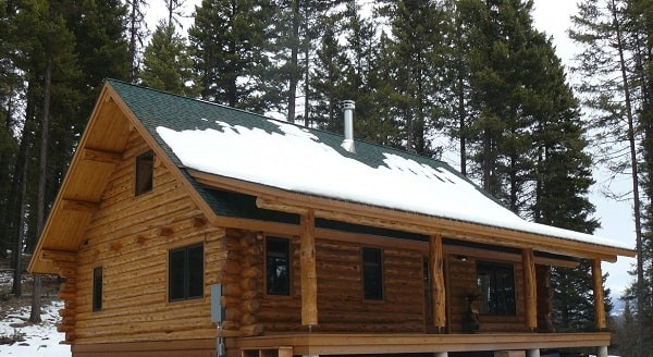 Right side view with gable roof and a covered deck framed with log columns.