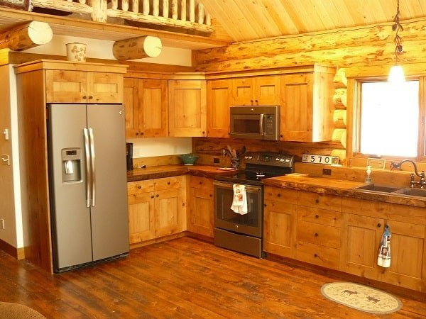 The kitchen has slate appliances, double bowl sink, and wooden cabinets that blend in with the hardwood floor and cathedral ceiling.