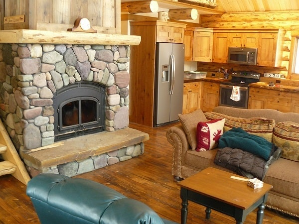 An open layout view showing the kitchen and living room warmed by a stone fireplace.