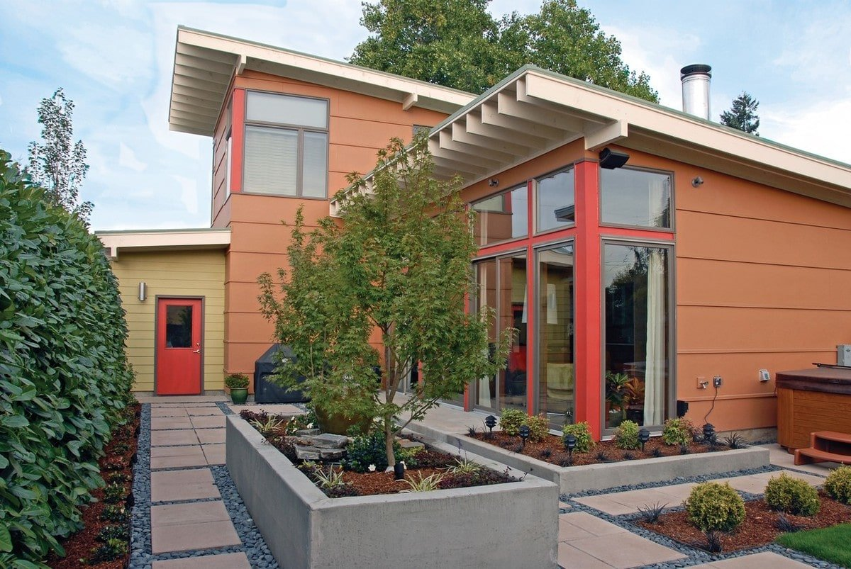 Side exterior view with a concrete planter and a vibrant red door leading to the double garage.