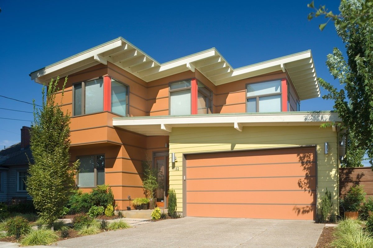 Home facade with warm horizontal siding, corner glass windows, and flat roofs.