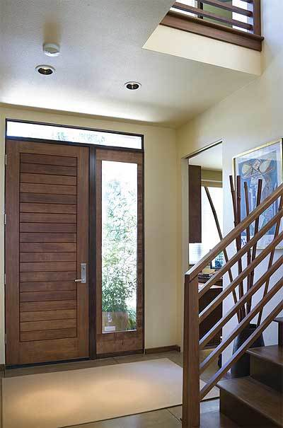 Foyer with a wooden front door, brown rug, and a framed artwork adorning the beige wall.