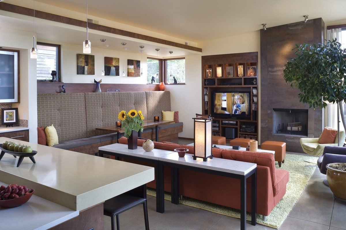 A dining area lies next to the living room while the kitchen is situated at the back of the terracotta sofa.