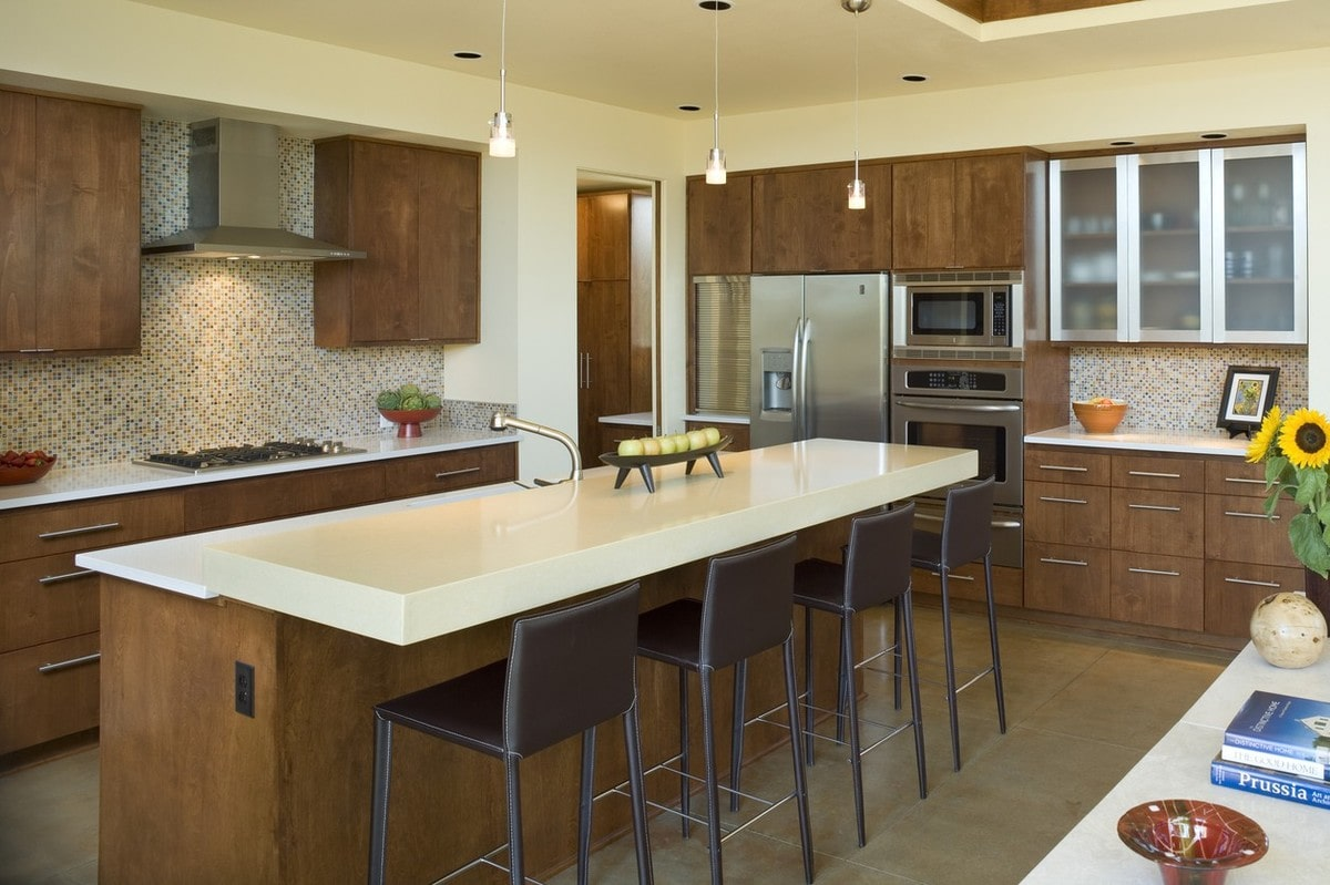 Kitchen with wooden cabinetry, stainless steel appliances, and a two-tier breakfast island lines with brown counter chairs.