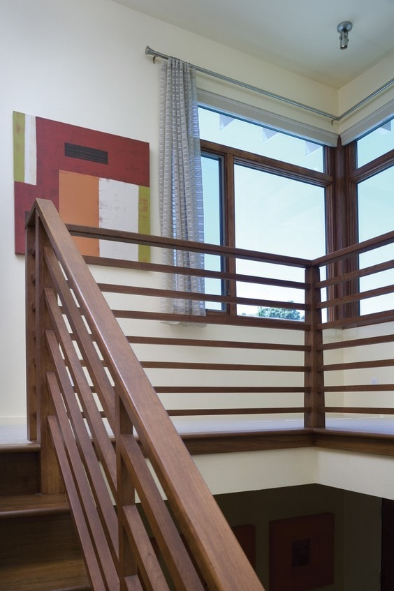 Second-floor balcony with wooden railings and white walls adorned with multi-colored artwork.