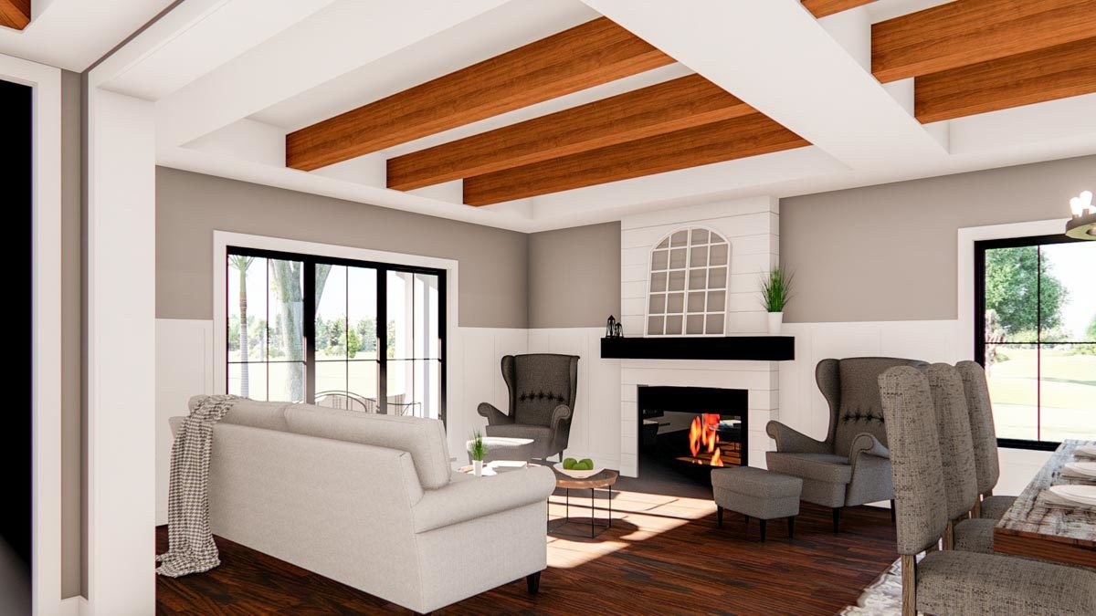 The living room has a gray sectional sofa, round coffee table, and wingback lounge chairs flanking the fireplace.