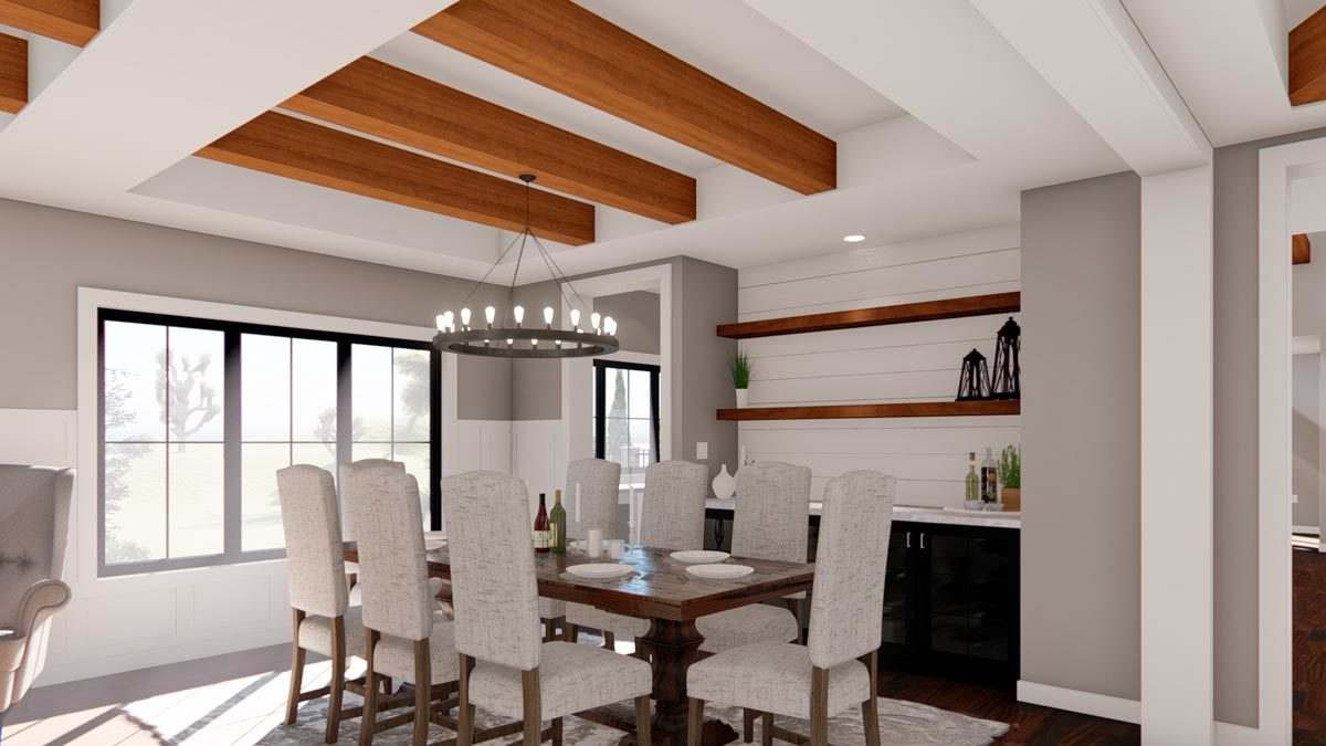 Dining room with a buffet bar, gray upholstered chairs, and a dark wood dining table well-lit by a round chandelier.