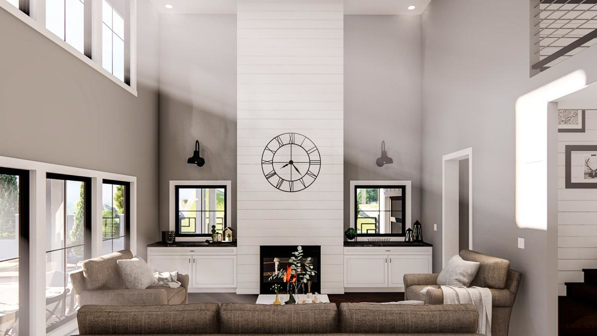 Great room with beige seats, built-in cabinets, and a fireplace topped with a wall clock.