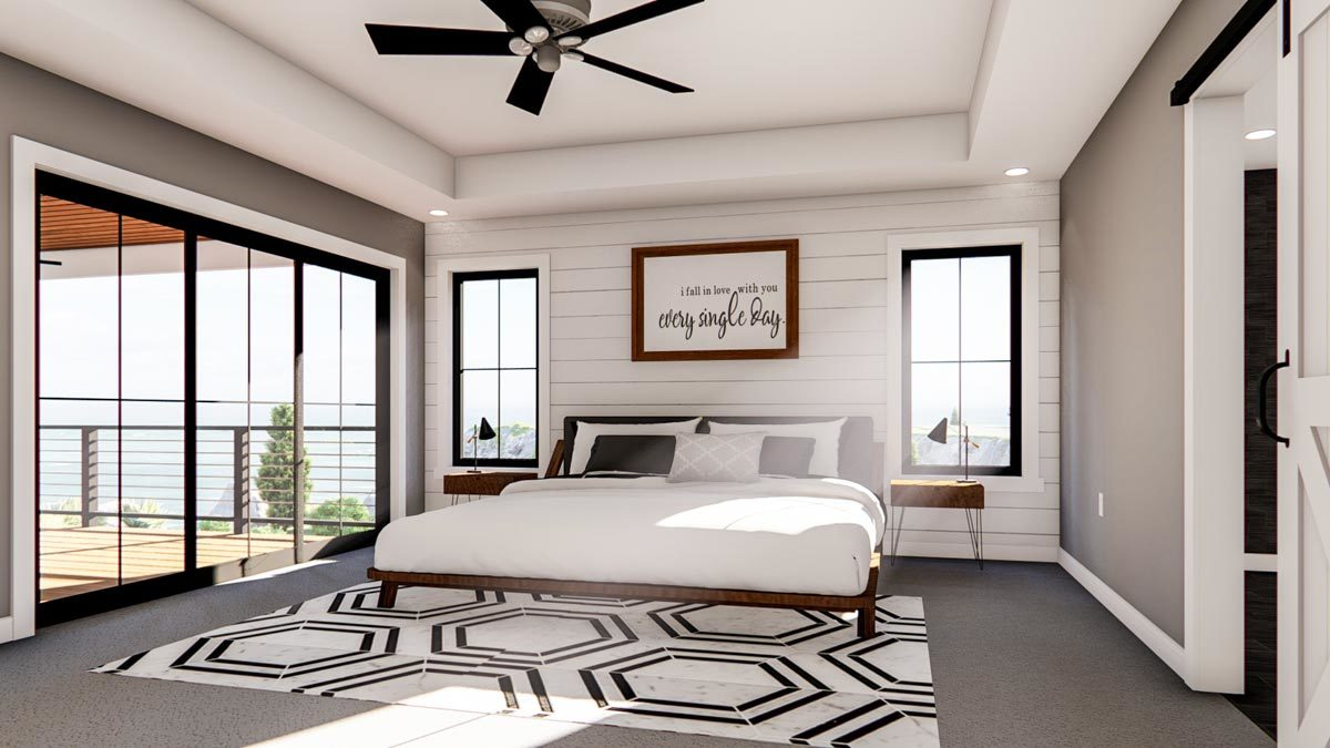 The primary bedroom has a tray ceiling, wooden furnishings, a geometric patterned rug, and a private deck.