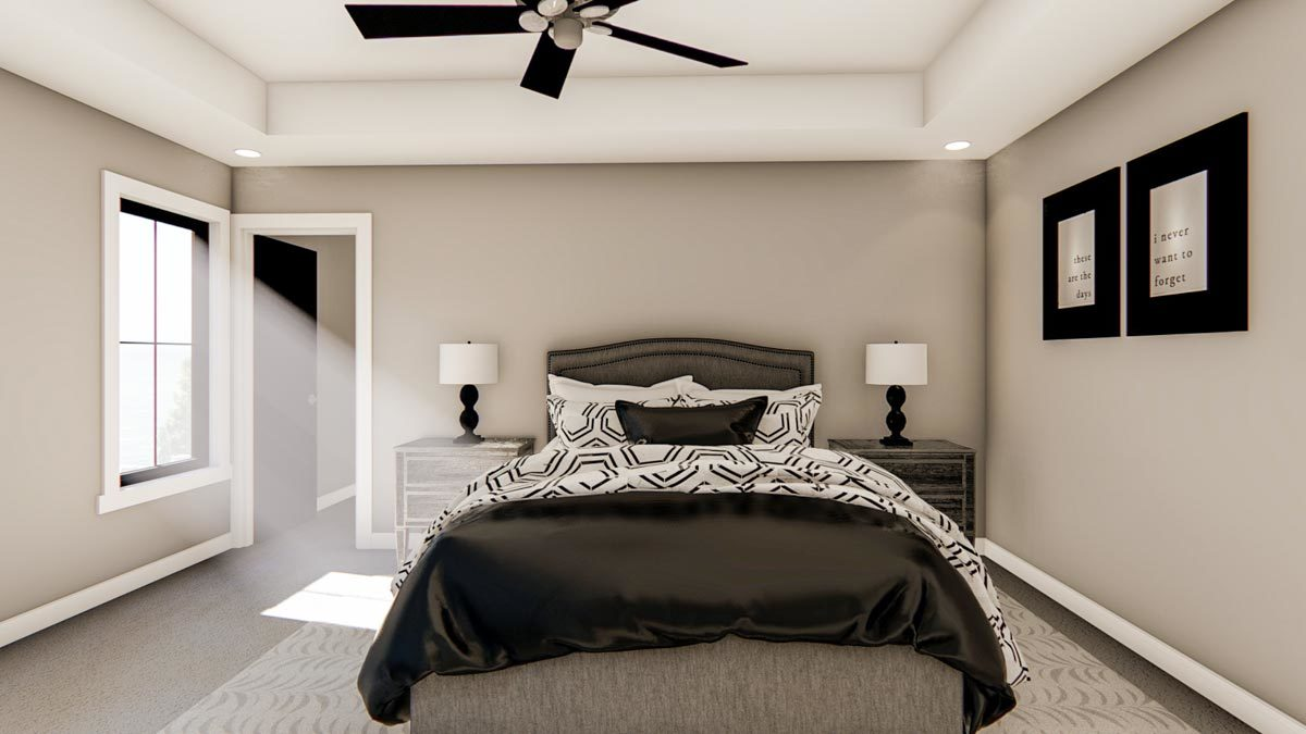 Bedroom with a ceiling fan, gray upholstered bed, rustic nightstands, and black-framed artworks adorning the gray wall.