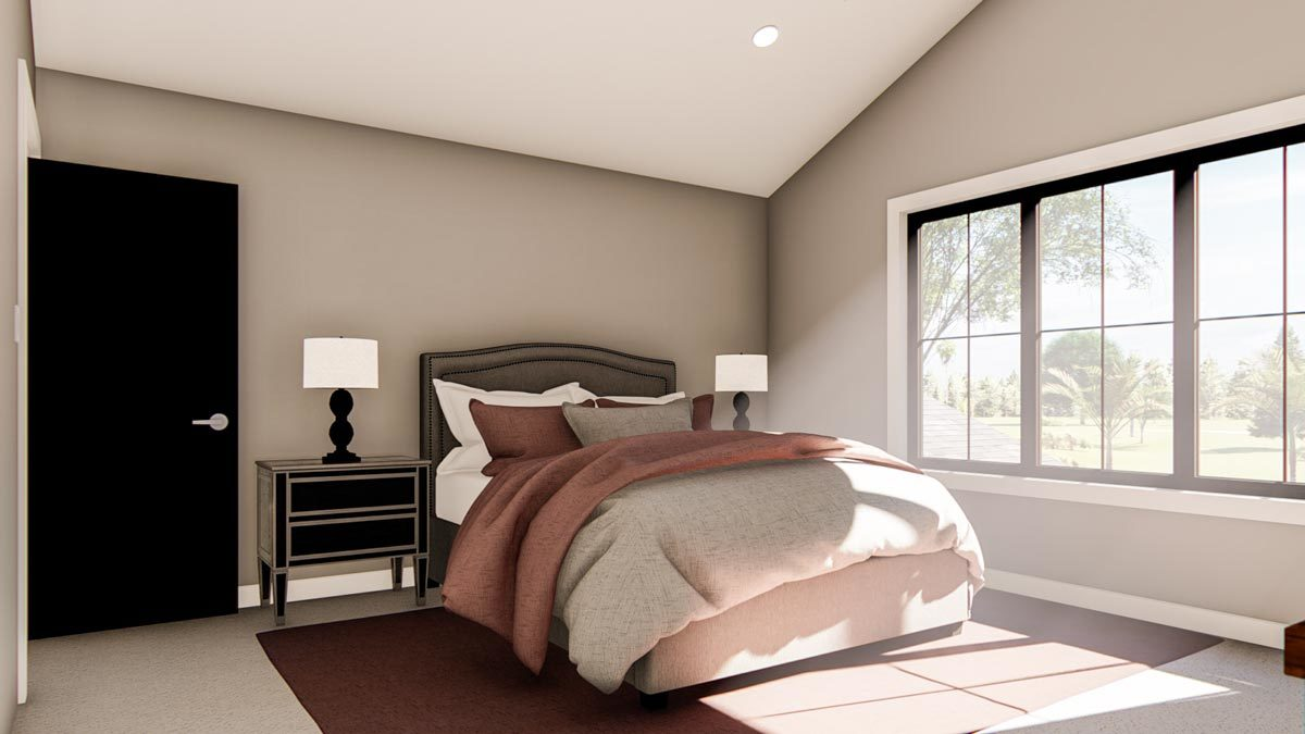 This bedroom has a vaulted ceiling, carpet flooring, and black aluminum-framed windows that invite natural light in.