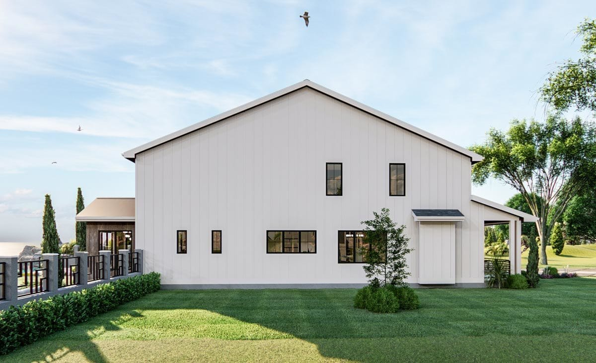 Left side view showing the white vertical siding that stands out against the lush green lawn.