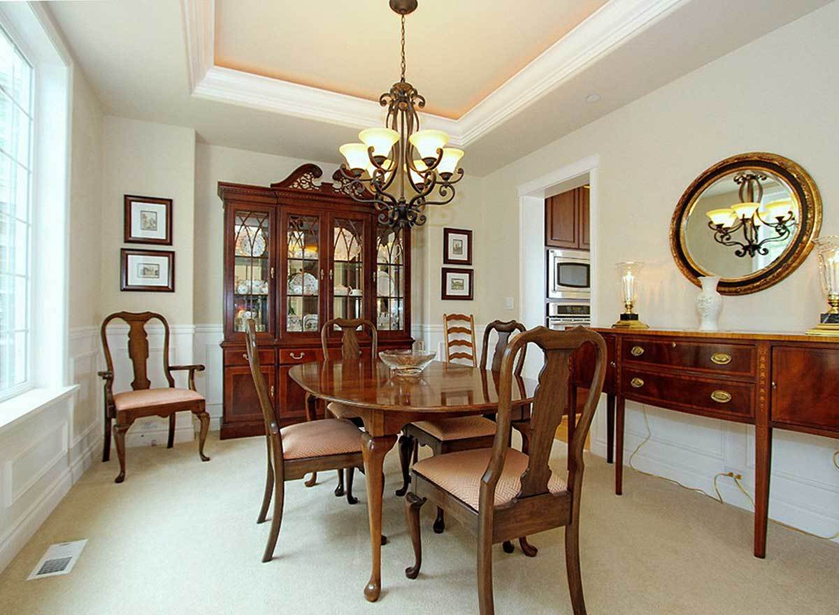 Formal dining room with a china cabinet, oval dining set, and a wooden buffet bar adorned with a round mirror.