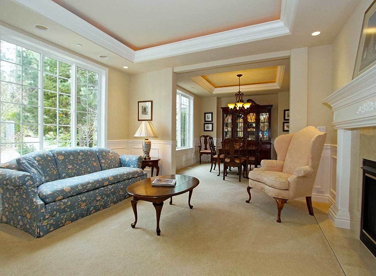 The living room offers a floral sofa, beige wingback chair, wooden tables, and a glass-enclosed fireplace.