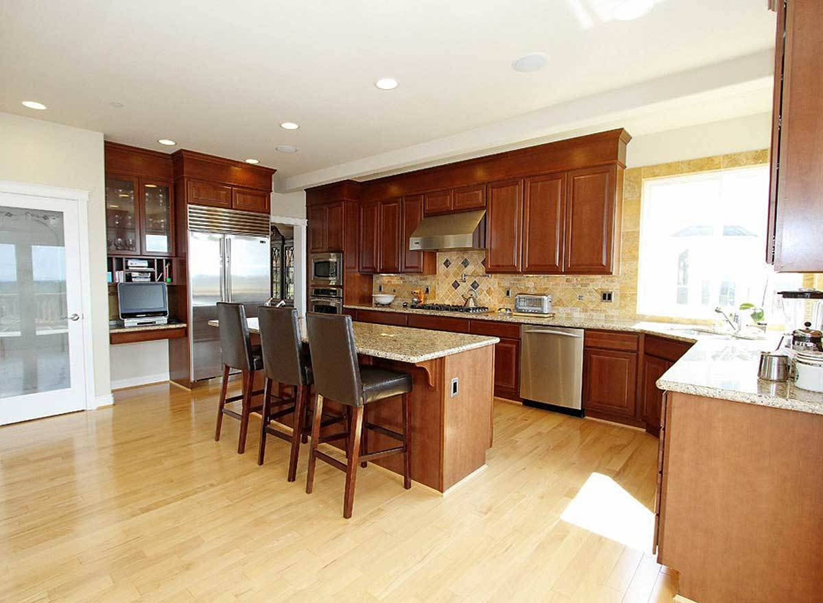 Kitchen with stainless steel appliances, wooden cabinetry, desk nook, and a center island lined with black leather counter chairs.