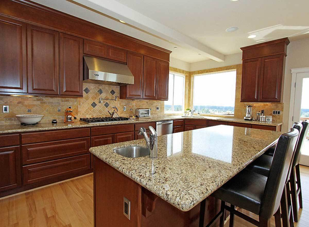 A closer look at the granite top island fitted with a small undermount sink.