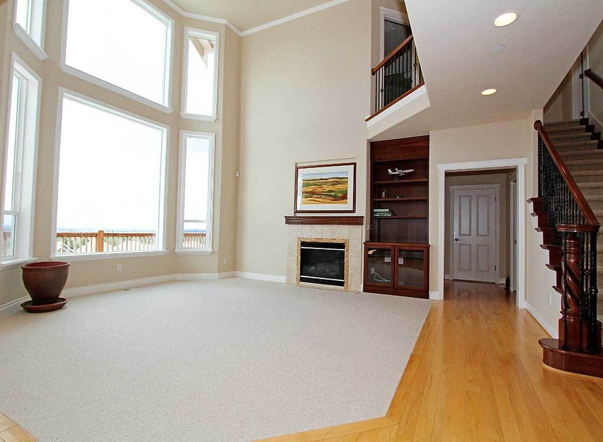 Spacious family room with a modern fireplace, inset built-in, and massive windows that bring an abundance amount of natural light in.