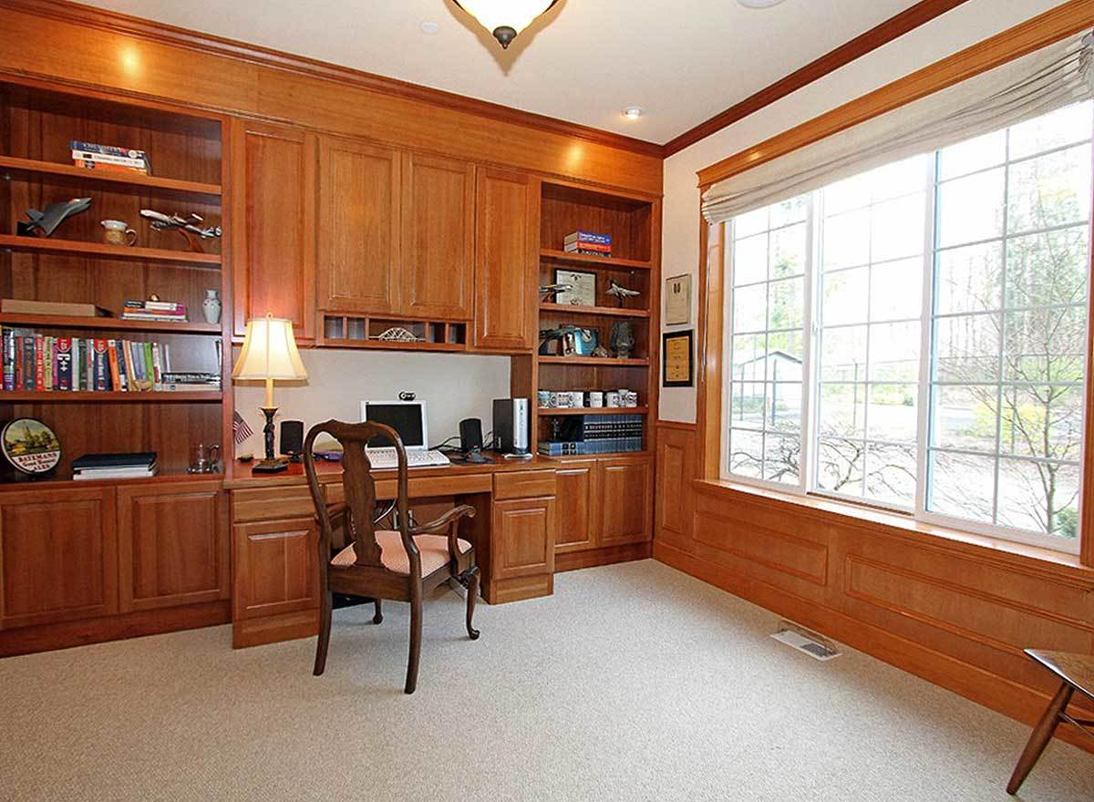 The home office showcases white framed windows, wooden built-ins, and a cozy cushioned armchair.