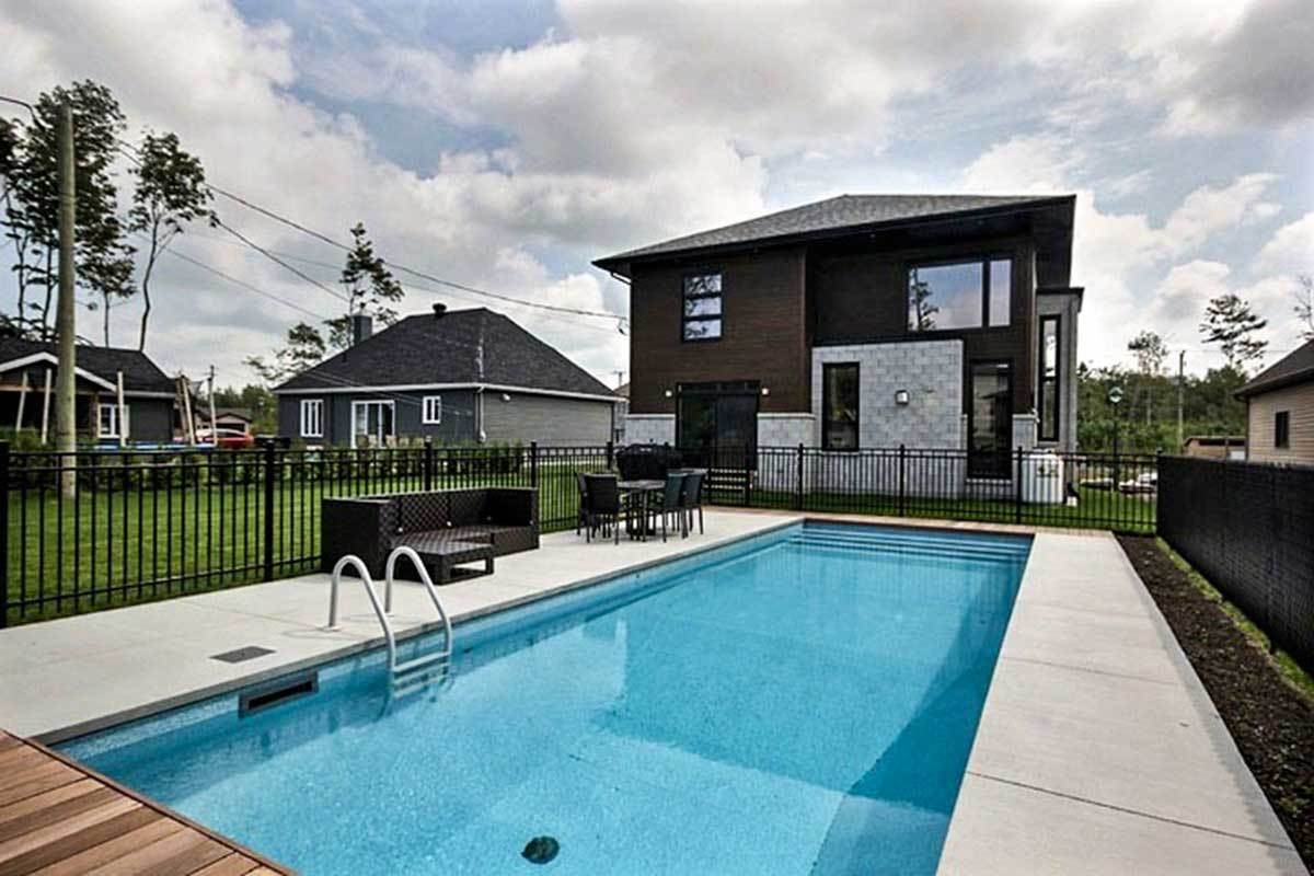 Rear exterior view boasting a lap swimming pool complemented with outdoor dining and seats.