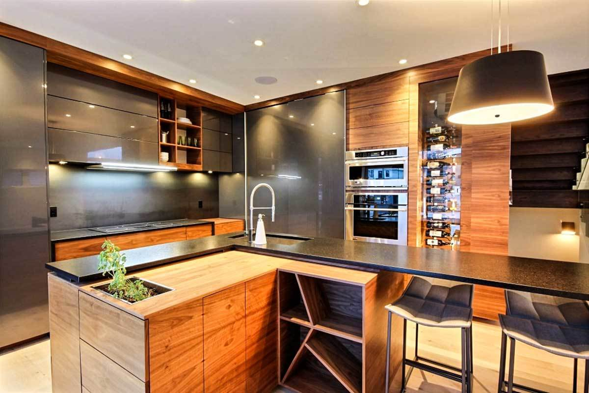 The kitchen is equipped with slate cabinets, an L-shaped island, and a glass-enclosed wine rack fitted on the wooden cabinet.
