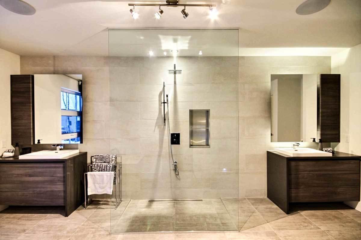 Primary bathroom with a walk-in shower nestled in between the wooden vanities.