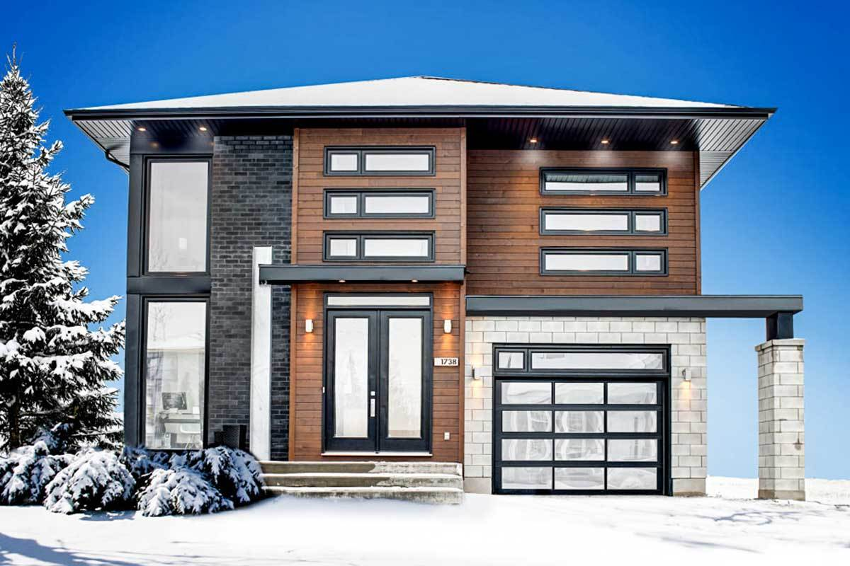 Front view of the house during winter showcasing its sleek and clean architectural design accentuated with stone brick and wood-paneled exterior.