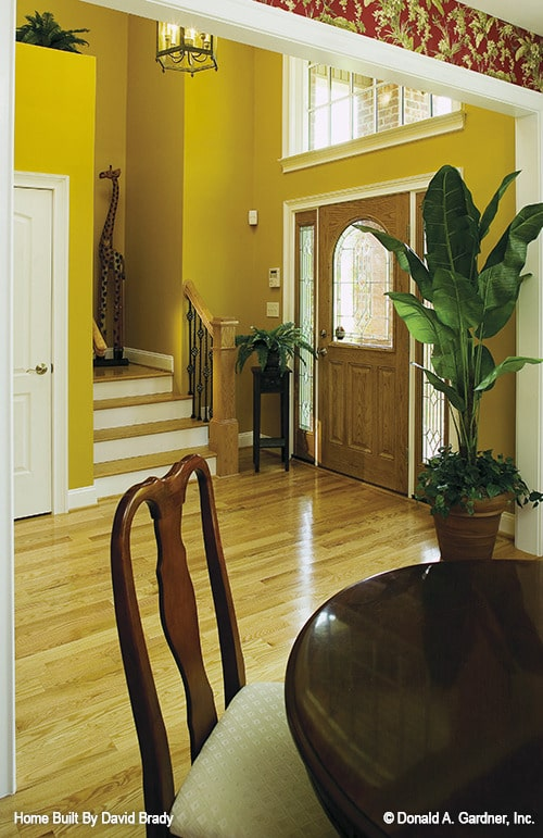 The foyer has vibrant yellow walls, a traditional staircase, and a wooden entry door fitted with stained glass panels.