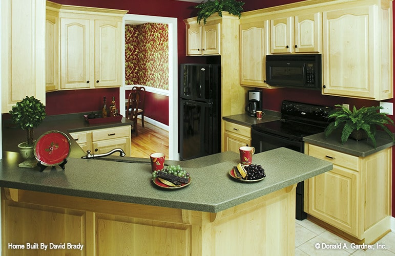The kitchen has cream cabinetry, black appliances, and a curved peninsula with two-tier countertops.